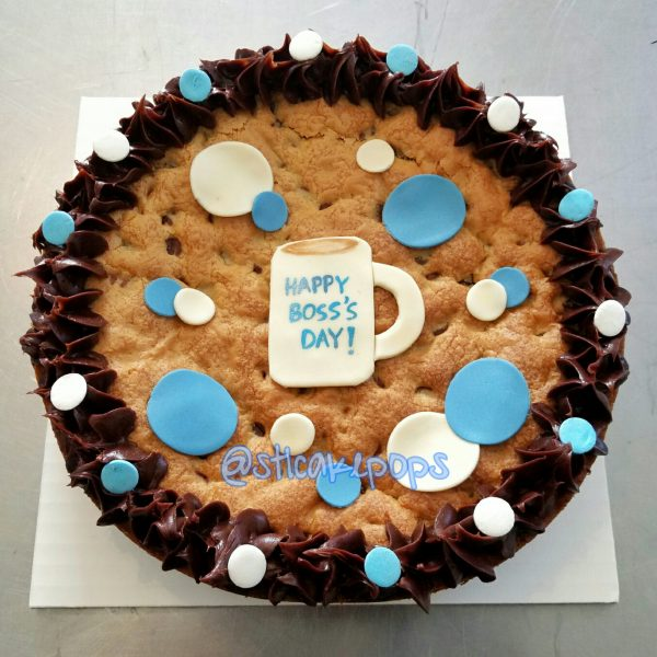 large chocolate chip cookie with blue, brown and white icing with a coffee mug decoration