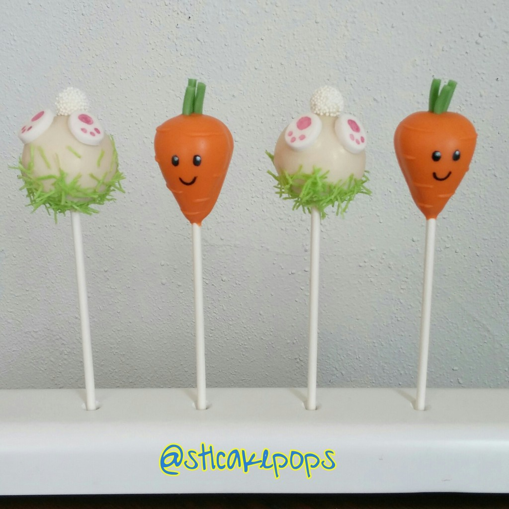 cake pops decorated as bunny bottoms in the grass and a carrot with a face on it.