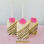 white chocolate covered rice crispy treat with black and yellow stripes and a pink flower